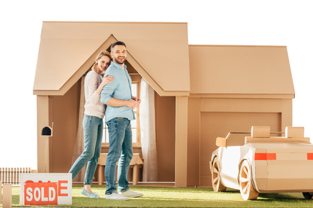 beautiful couple in front of their new cardboard house isolated on white