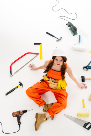 overhead view of girl in overalls sitting on floor with different equipment and tools, isolated on white