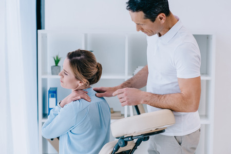 masseur  looking at client with neckpain at office