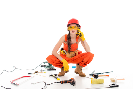 workwoman in overalls sitting on floor with different equipment and tools, isolated on white Фото со стока