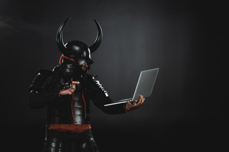 side view of armored samurai using laptop on black Banco de Imagens