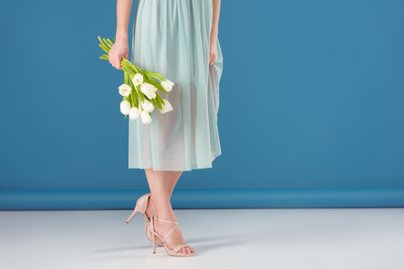 cropped image of girl holding bouquet of tulips on blue