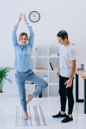 businesswoman with her trainer practicing yoga in tree pose at office