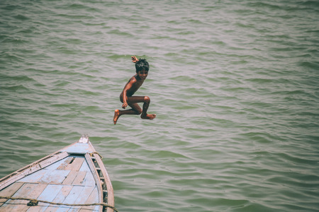 adorable little boy jumping from boat in Varanasi, India Stock Photo