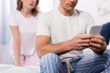 partial view of man using smartphone with wife standing behind at home Standard-Bild - 114248606