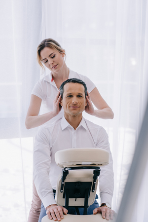 masseuse doing head massage for handsome mature businessman