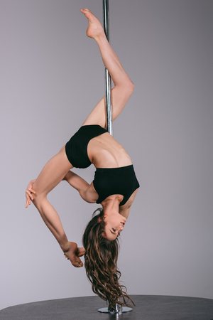 beautiful flexible pole dancer exercising with pylon and looking away on grey