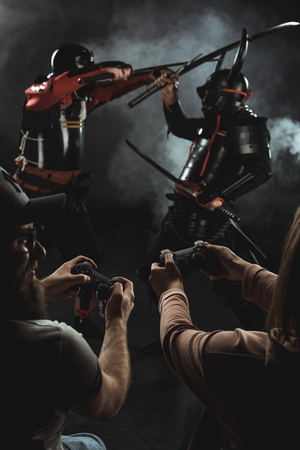 back view of man and woman playing samurai fighting in real life with gamepads on black Stok Fotoğraf - 114248831