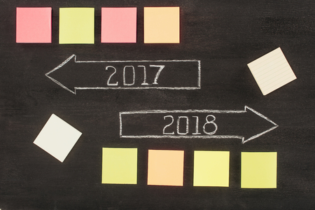 top view of arranged empty sticky notes and arrows with 2017, 2018 year signs on dark wooden surface