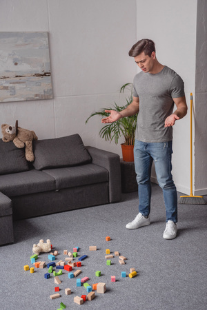 man standing in living room and looking at children toys scattered on floor