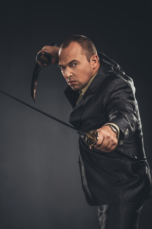 man in defence pose in suit with katana swords on black Stock Photo