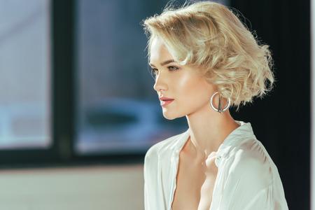 Portrait d'une belle femme blonde en chemise blanche regardant loin à l'intérieur