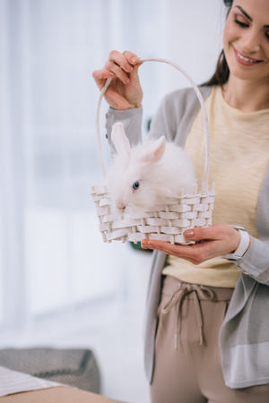attractive young woman with white rabbit in basket