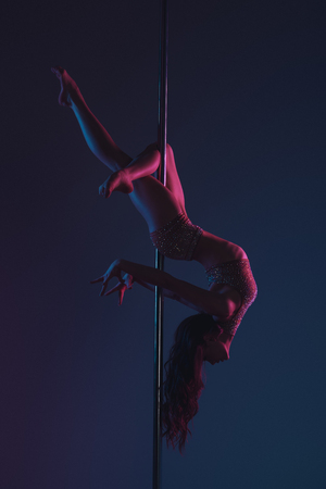 beautiful flexible young woman exercising with pole on blue