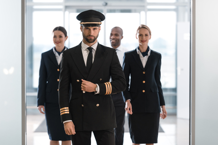 handsome pilot at airport with his team looking at camera