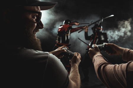 close-up shot of happy bearded man and woman playing samurai fighting in real life with gamepads on black Stok Fotoğraf