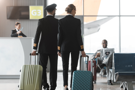 back view of male and female pilots walking by airport lobby with suitcases