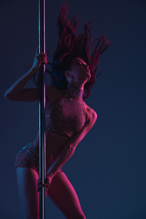 beautiful seductive young woman dancing with pole on blue 版權商用圖片