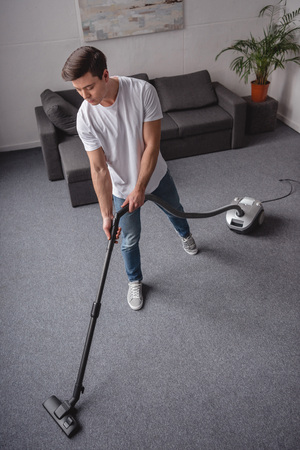 high angle view of handsome man cleaning living room with vacuum cleaner 스톡 콘텐츠