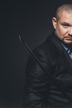close-up shot of modern samurai with katana sword on black 写真素材