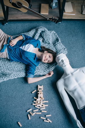 overhead view of woman and mannequin lying on floor near blocks wood game, perfect relationship dream concept Foto de archivo
