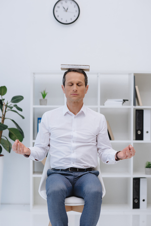 adult businessman meditating with book on head at office Foto de archivo