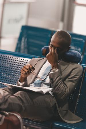 sleepy businessman with travel pillow waiting for flight at airport lobby Standard-Bild - 114249296