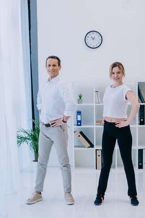 happy mature businessman warming up before workout with female personal trainer