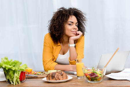 young african american woman leaning on table with various food and laptop, freelance concept