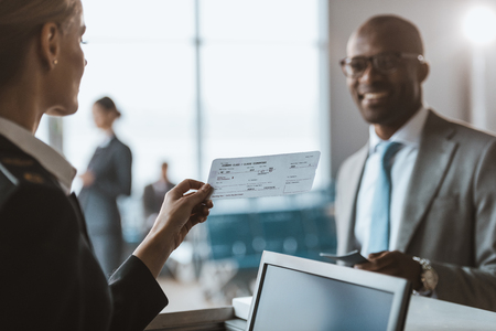 close-up shot of smiling african american businessman giving passport to staff at airport check in counter Stockfoto - 114249305