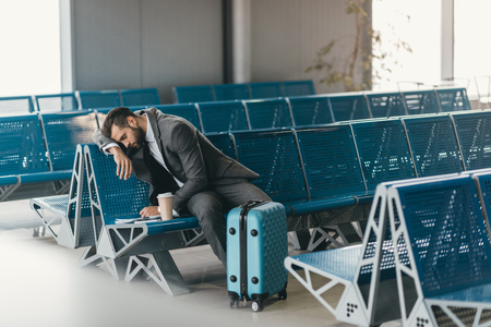 sleepy young businessman waiting for flight at airport lobby Imagens