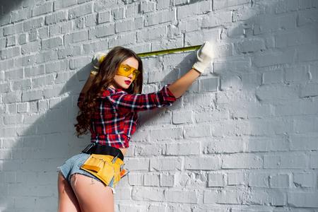 Mujer en gafas con cinturón de herramientas de medición de pared de ladrillo blanco.