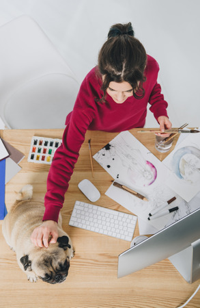 Young woman cuddling pug dog while working on designs by table Imagens