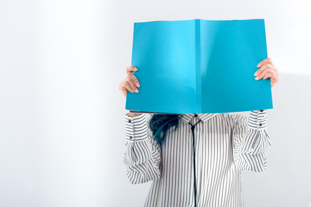 Woman reading and holding book over her face