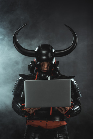 armored samurai warrior using laptop on dark background with smoke Banco de Imagens
