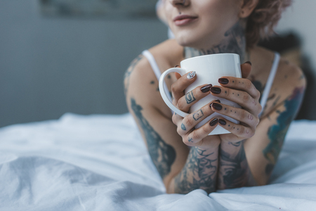 cropped view of tattooed girl drinking coffee in bed at morning
