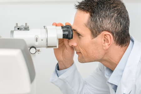 side view of professional optometrist working with slit lamp in clinic