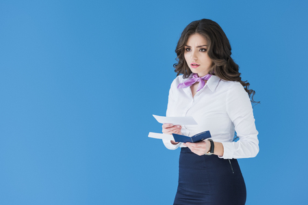 beautiful stewardess holding tickets and passport isolated on blue