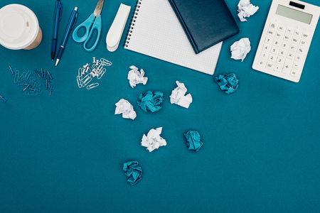 top view of crumpled papers, calculator and office supplies on blue 写真素材