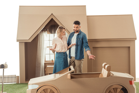man presenting cardboard car to his wife for birthday isolated on white