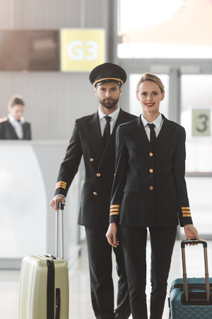 happy male and female pilots walking by airport lobby with suitcases 免版税图像
