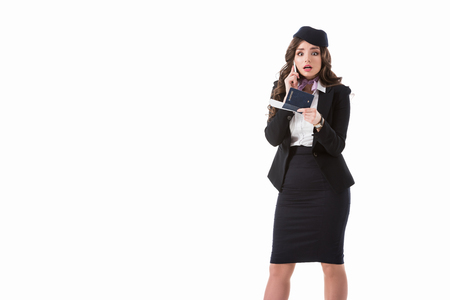 shocked stewardess talking by smartphone and holding passport isolated on white Stock Photo