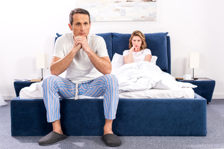 upset man sitting on bed with wife behind at home, relationship difficulties concept Standard-Bild - 114249617