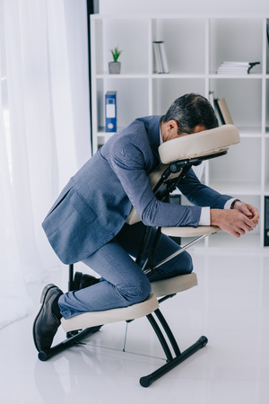 businessman in suit sitting in massage chair at office Фото со стока - 114249624