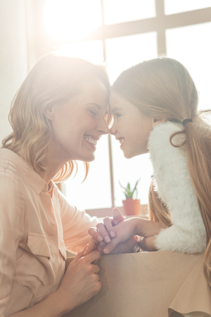 happy mother and daughter cuddling in front of light window Stock fotó