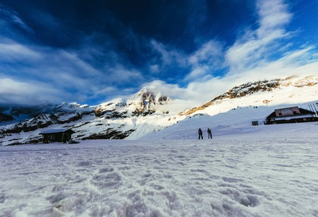 tranquil mountains landscape under blue sky with tourists walking on snow, Austria