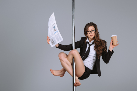 young businesswoman in eyeglasses holding newspaper and coffee to go, hanging on pole and looking at camera on grey 免版税图像