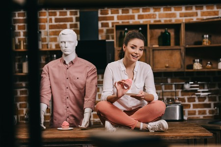 woman with cupcake sitting on table with mannequin behind, loneliness concept