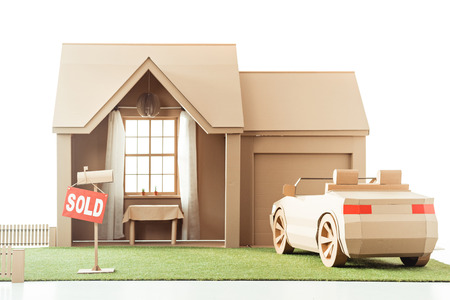 cardboard house and car with sign sold isolated on white Banco de Imagens