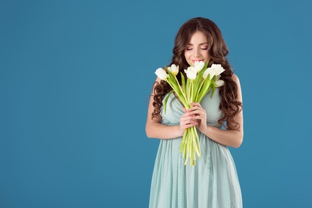 beautiful girl sniffing tulips isolated on blue Banco de Imagens